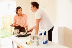 Молодые пары украшая комнату смотря один другого Стоковые Фотографии RF