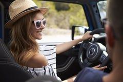 Молодые пары управляя открытым верхним автомобилем на проселочной дороге Стоковое фото RF