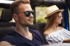 Молодые пары управляя открытым верхним автомобилем на проселочной дороге Стоковое Фото
