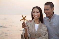 Молодые пары усмехаясь и смотря Seashell Стоковая Фотография RF