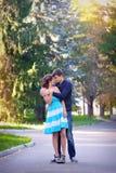 Молодые пары целуя пока сидящ в лесе лета Стоковая Фотография RF