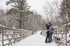 Молодые пары целуя outdoors в зиме Стоковое Фото