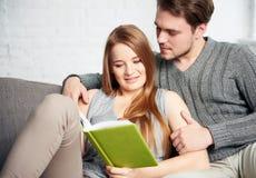 Молодые пары читая книгу на софе Стоковые Фотографии RF