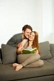 Молодые пары читая книгу на софе Стоковые Изображения RF