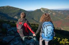 Молодые пары backpackers наслаждаясь красивым ландшафтом Стоковые Фотографии RF