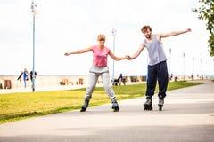 Молодые пары rollerblading в парке держа руки Стоковое фото RF