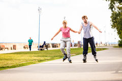 Молодые пары rollerblading в парке держа руки Стоковые Изображения