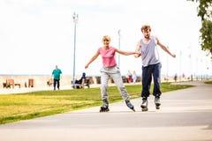 Молодые пары rollerblading в парке держа руки Стоковые Фото