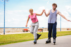 Молодые пары rollerblading в парке держа руки Стоковая Фотография