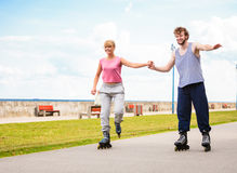 Молодые пары rollerblading в парке держа руки Стоковые Изображения RF