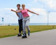 Молодые пары rollerblading совместно Стоковые Фото