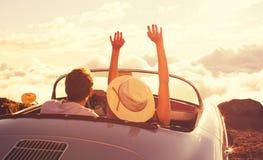 Молодые пары Wathcing заход солнца в винтажном автомобиле спорт