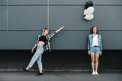 Молодые подруги представляя с пуком воздушных шаров outdoors Стоковая Фотография RF