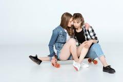 Молодые подруги сидя совместно на скейтборде и говорить Стоковое Изображение