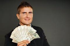 Молодые представления бизнесмена с деньгами Стоковая Фотография