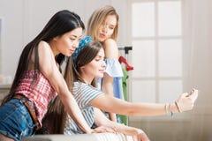Молодые привлекательные девушки представляя и принимая selfie на smartphone дома Стоковая Фотография RF