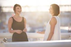 Молодые привлекательные девушки стоя outdoors на мосте смеясь над совместно Стоковые Фотографии RF