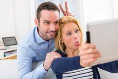 Молодые привлекательные пары имея потеху делая selfie Стоковые Фото