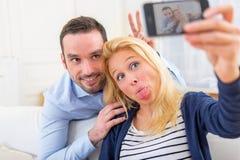 Молодые привлекательные пары имея потеху делая selfie Стоковые Изображения