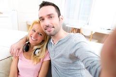 Молодые привлекательные пары имея потеху делая selfie Стоковое Фото