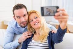 Молодые привлекательные пары имея потеху делая selfie Стоковое Изображение