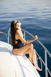 Молодые привлекательные представления женщины на роскошную яхту плавая на море Стоковая Фотография