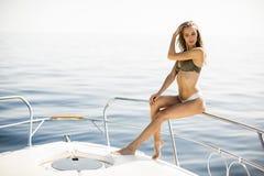 Молодые привлекательные представления женщины на роскошную яхту плавая на море Стоковая Фотография RF