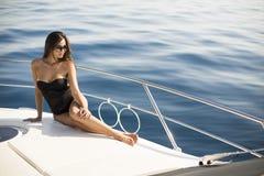 Молодые привлекательные представления женщины на роскошную яхту плавая на море Стоковые Изображения RF