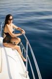 Молодые привлекательные представления женщины на роскошную яхту плавая на море Стоковые Изображения