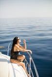 Молодые привлекательные представления женщины на роскошную яхту плавая на море Стоковое фото RF