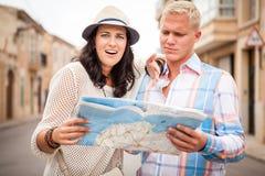 Молодые привлекательные туристские пары с городом составляют карту в лете Стоковые Фотографии RF