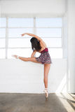 Молодые простирания себя женщины танцора около окна Стоковая Фотография RF