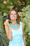 Молодые пузыри мыла красивой и счастливой девушки дуя к воздуху на предпосылке зеленого парка естественной в концепции очарования Стоковая Фотография RF