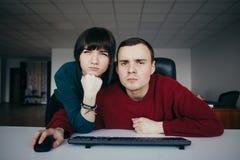 Молодые работники офиса смотря близко на камере в рабочем месте Эмоциональное красивое молодые люди в рабочем месте Стоковые Фото