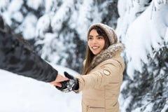 Молодые романтичные пары идя в руку человека владением женщины леса снега внешнюю азиатскую следовать мной Стоковые Фотографии RF
