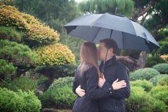 Молодые романтичные пары при зонтик целуя в дожде Стоковое Изображение