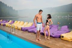 Молодые романтичные пары при совершенные тела стоя близко бассейн стоковое фото
