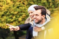 Молодые романтичные пары указывая в парк в осени Стоковые Фото