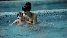 Молодые родители в бассейне уча, что его сын поплавал под водой видеоматериал