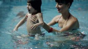 Молодые родители в бассейне уча, что его сын поплавал под водой акции видеоматериалы