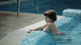 Молодые родители играя с его сыном в бассейне сток-видео