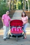 Молодые родители и их 2 маленьких дет в двойной прогулочной коляске Стоковые Фотографии RF