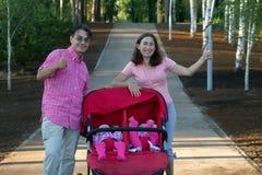 Молодые родители и их 2 маленьких дет в двойной прогулочной коляске Стоковое Фото