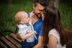 Молодые родители и маленький сын в семье парка счастливой сидя на стенде Стоковое Изображение