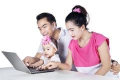 Молодые родители и ребенок смотря компьтер-книжку Стоковое фото RF
