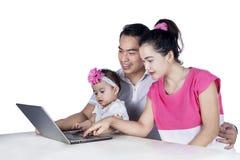 Молодые родители и ребенок смотря компьтер-книжку Стоковое Фото