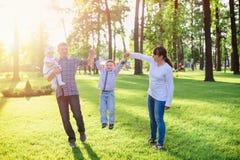 Молодые родители с детьми идут в парк лета Стоковые Фотографии RF