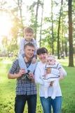 Молодые родители с детьми идут в парк лета Стоковые Изображения RF