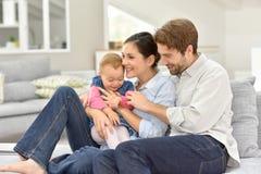 Молодые родители с младенцем на софе Стоковая Фотография