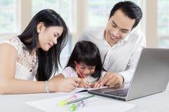 Молодые родители учат их ребенку дома Стоковая Фотография RF